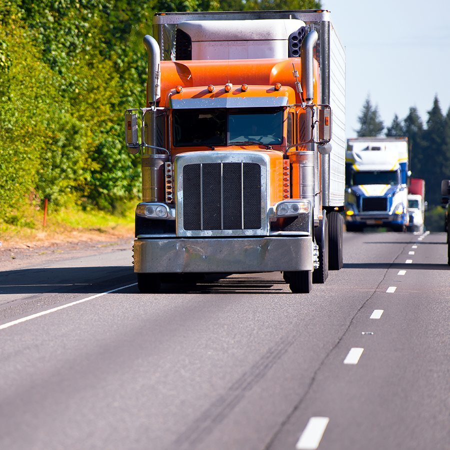 Classic orange semi truck with a refrigerator on a multilane highway road ahead of a convoy of trucks with trailers moving in the right lane highway on a background of green trees and bushes. Movement on the modern highway assures transportation of various goods on these trucks.